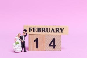 sposa e sposo in miniatura su uno sfondo rosa, il giorno di San Valentino e il concetto di matrimonio foto