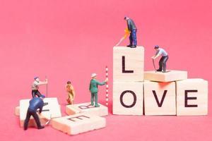 lavoratore in miniatura collaborando per costruire la parola amore su blocchi di legno con uno sfondo rosa, concetto di San Valentino
