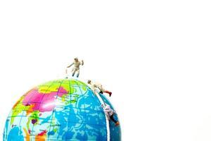 escursionisti in miniatura che si arrampicano sul concetto di globo, sport e tempo libero foto