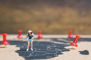 zaino in spalla in miniatura che cammina su una mappa del mondo, turismo e concetto di viaggio foto