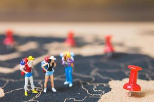 backpackers in miniatura che camminano su una mappa del mondo, turismo e concetto di viaggio foto