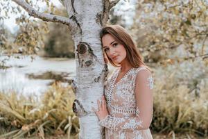 donna in posa contro un albero in un vestito