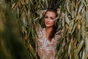 donna che indossa un abito in pizzo contro le foglie foto