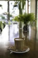 latte in un bicchiere su una scrivania in legno foto