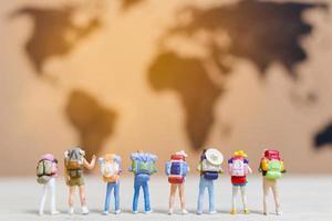 viaggiatori in miniatura che camminano su una mappa del mondo, viaggiano ed esplorano il concetto di mondo foto