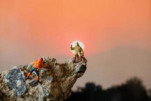 escursionisti in miniatura che si arrampicano su una roccia, sport e concetto di tempo libero foto
