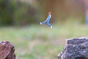 persone in miniatura in esecuzione su una scogliera rocciosa con sfondo della natura, concetto di salute e stile di vita foto
