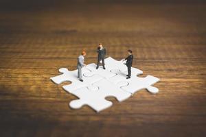 uomini d'affari in miniatura in piedi su seghetti alternativi con uno sfondo di legno, concetto di affari foto