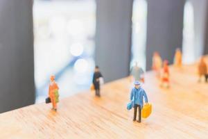 viaggiatori in miniatura che camminano su un pavimento in legno, vacanza e concetto di viaggio