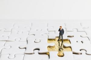 imprenditore in miniatura in piedi su un puzzle bianco, concetto di business foto