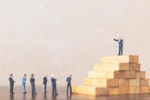 uomini d'affari in miniatura in piedi su un blocco di legno, leader aziendale di successo e concetto di lavoro di squadra foto