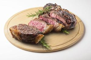 bistecca fiorentina tagliata su tagliere tondo in legno foto