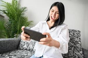 donna divertendosi giocando sullo smartphone foto