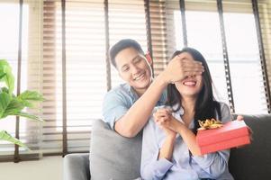 uomo asiatico dando confezione regalo presente per sorprendere la sua ragazza foto