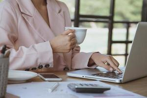 imprenditrice bere caffè e guardando attraverso il computer portatile foto
