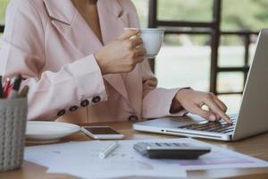 imprenditrice con bere caffè e guardando attraverso il computer portatile foto