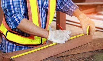 carpentiere che misura il legno foto