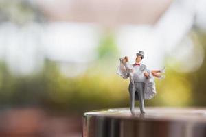 coppia di sposi in miniatura in piedi su un palco, concetto di matrimonio foto