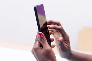 mani della donna che tengono un telefono cellulare foto