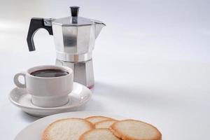caffettiera con tazza colazione bianca e biscotti foto