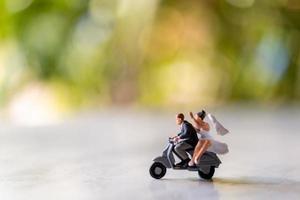 sposa e sposo in miniatura all'aperto con uno sfondo verde bokeh foto