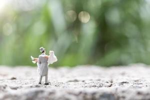 sposa e sposo in miniatura in piedi all'aperto con uno sfondo sfocato della natura foto