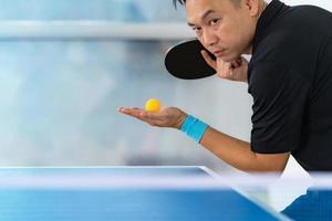 maschio giocando a ping pong con racchetta e palla in un palazzetto dello sport foto