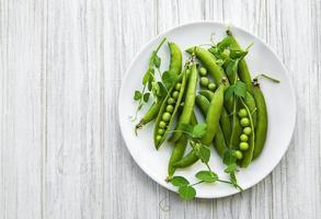 piselli verdi in un piatto su uno sfondo bianco di legno foto