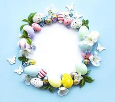 uova di Pasqua, fiori colorati su sfondo blu pastello
