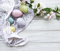 sacchetto di stringa con uova di Pasqua e fiori primaverili foto
