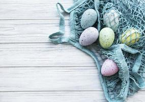 sacchetto di stringa con uova di Pasqua e fiori primaverili