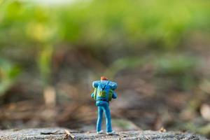 viaggiatore in miniatura con uno zaino che cammina in un prato, viaggi e concetto di avventura foto