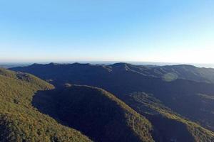 veduta aerea di un paesaggio di montagna con un cielo blu chiaro foto