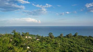 Seascape con case e campi verdi accanto a un corpo idrico con nuvoloso cielo blu a New Athos, Abkhazia, Georgia foto