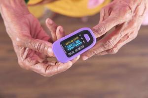 mano della donna senior utilizzando il pulsossimetro foto