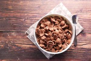 vista dall'alto di fiocchi di mais al cioccolato in una ciotola su sfondo di legno foto