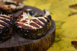 bistecche di pesce fritte alla griglia sdraiato sul tronco d'albero
