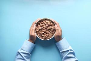 vista dall'alto di fiocchi di mais al cioccolato in una ciotola su sfondo blu foto