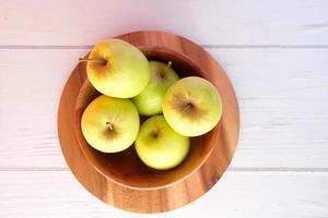 vista dall'alto di mele verdi fresche in una ciotola di legno foto