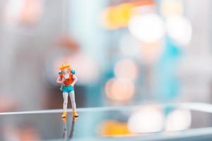 persone in miniatura di turisti zaino in spalla in piedi su uno smartphone, concetto di viaggio