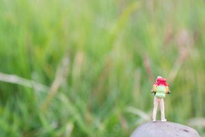 viaggiatore in miniatura con uno zaino in piedi e camminare in un prato foto