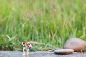 viaggiatori in miniatura con zaini in piedi e camminando in un prato foto