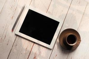 composizione piatta di tavoletta digitale e tè su fondo in legno foto