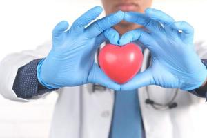 mano del medico in guanti protettivi che tengono cuore rosso foto