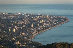 vista aerea delle montagne e della città lontana vicino al corpo d'acqua a sochi, russia foto