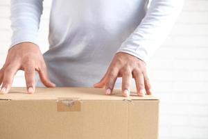mano d'uomo aprendo una scatola di cartone foto
