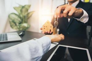 immobiliare e casa di vendita concetto, agente di banca dà la chiave al cliente foto