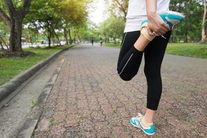 donna sportiva esercizi e si riscalda nel parco al mattino foto