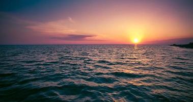vista sul mare con tramonto colorato, montagne e mare foto