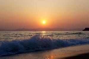 onde che si infrangono su una spiaggia con tramonto nuvoloso arancione sulle montagne foto